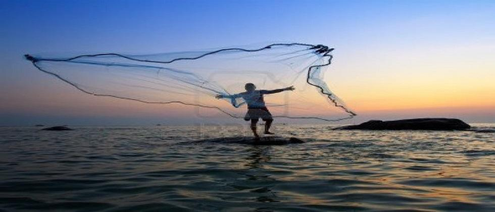 A fisherman falls into the sea while pulling a net