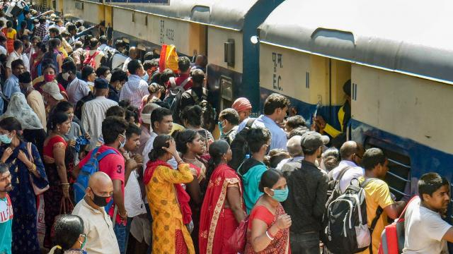 People board a train to reach their native places after further ease in COVID-19 lockdown restrictions, at Patna junction, Wednesday, July 14, 2021. (PTI)