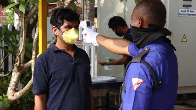 File photo of a worker being screened using a thermal gun before entering his work place at Verna industrial area.