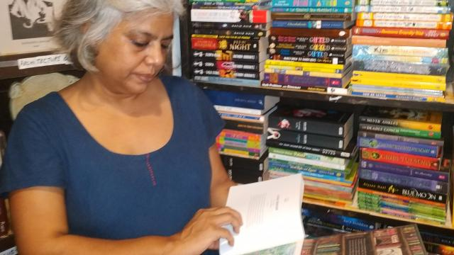 Diviya Kapur scanning through a book at Literati bookshop and cafe at Calangute.