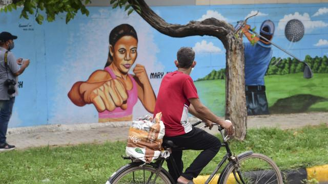 A cyclist walks past graffiti depicting Indian athlete participants in Tokyo Olympics 2020