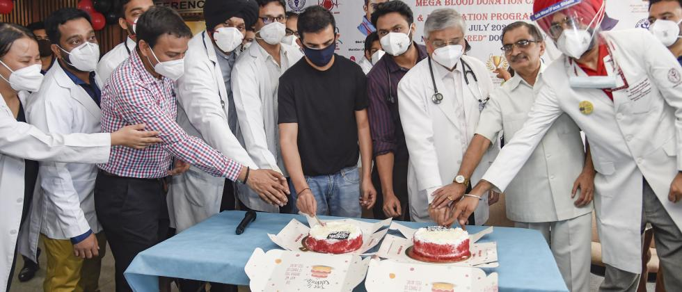 BJP MP Gautam Gambhir, AIIMS Director Dr. Randeep Guleria and staff cut cakes during the inauguration of an event to celebrate National Doctors Day, at AIIMS Hospital in New Delhi, Thursday, July 1, 2021. (PTI Photo)