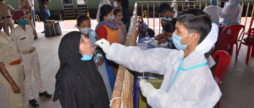 Passengers give their swab samples for COVID-19 tests after arriving at the railway station.  (PTI)