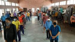 Migrant workers stand in a queue for registration to go back home. File Photo