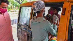 A youth looks at a medical staff as she inoculates his mother sitting inside a taxi with a dose of the Covishield AstraZeneca-Oxford's Covid-19 coronavirus vaccine at a drive-in vaccination facility in Mumbai July 13, 2021. (AFP)