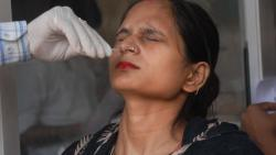 A health workers takes swab sample of a woman for COVID-19 test, at Disrict hospital in Noida, Tuesday, Oct. 5, 2021.