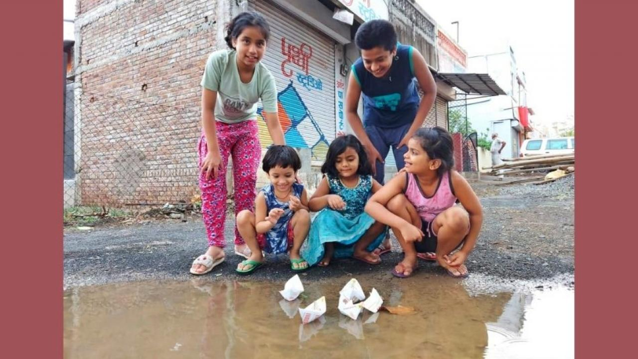 Children enjoying the pre monsoon rains by dropping paper boats