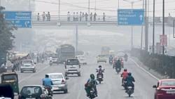 Motorists drive on a busy road as smog covers the skyline in New Delhi.