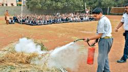 Student conducts the demo of extinguishning fire as the fire brigade officers supervise at Vidya Pratishthan's New English Medium School.