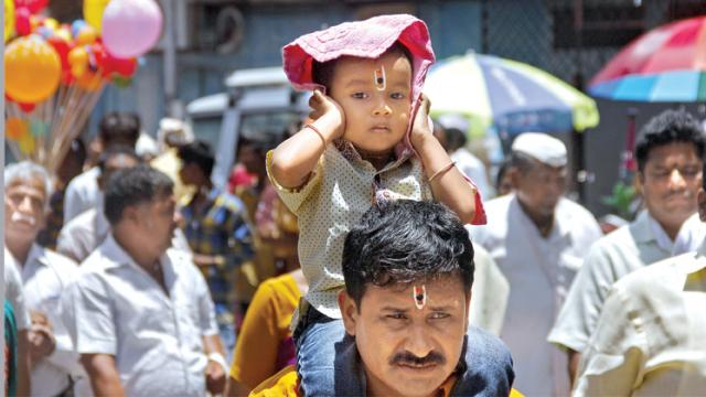 A child who came to visit the palkhis in Bhawani Peth covers his head with a handkerchief in order to protect himself from hot sun on Monday.