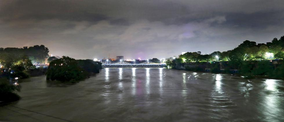 IN SPATE: A flooded Mutha river illuminated by the Chhatrapati Shahu Bridge next to Dengale Bridge. (Pic: Anand Chaini)