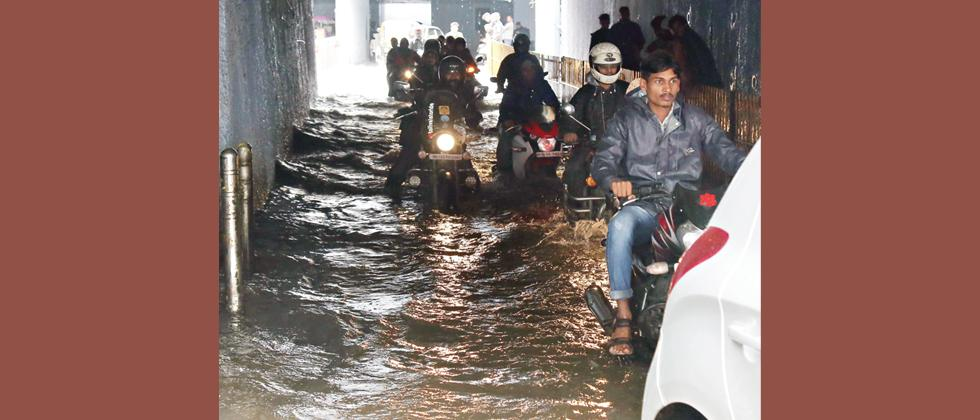 RIDING OR BOATING? Commuters ride through water after the Wakdewadi subway was flooded on Monday. (Pic: Anand Chaini)