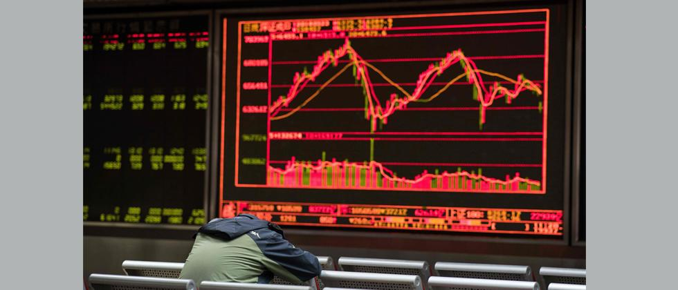 A man rests as he keeps an eye on stock price movements displayed on a screen at a securities company in Beijing on March 23, 2018.
