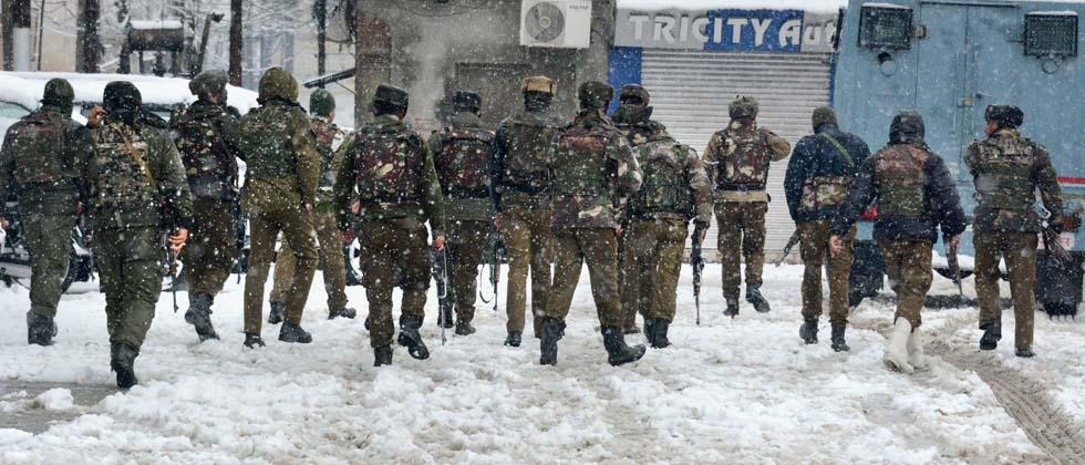 Special Operation Group (SOG) of Jammu and Kashmir Police personnel move towards the building where militants were hiding during an encounter, near a CRPF camp at Karra Nagar in Srinagar on Monday. PTI Photo