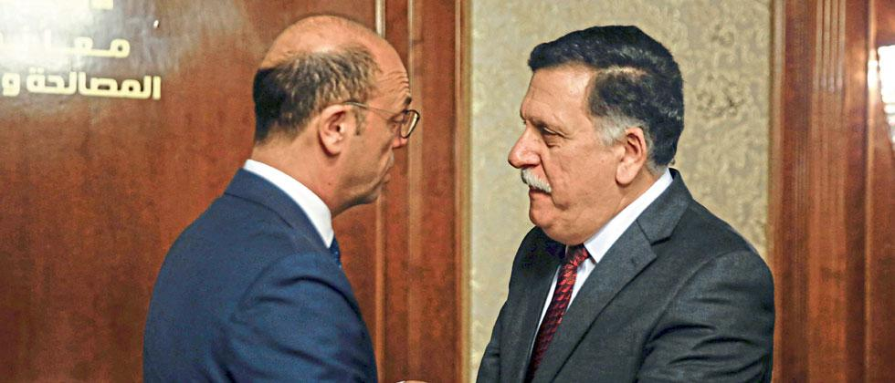 Libya's unity government PM Fayez al-Sarraj (R) greets Italy's Foreign Minister Angelino Alfano. According to Time, the Libyan Coast Guard was supported with funds from the EU, specifically Italy, to crack down on boats smuggling refugees to Europe