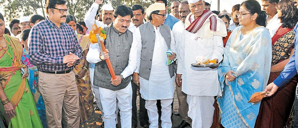Minister of Water Supply and Sanitation Babanrao Lonikar holding an axe at the event of laying foundation stone to provide clean water through taps in Shikrapur village