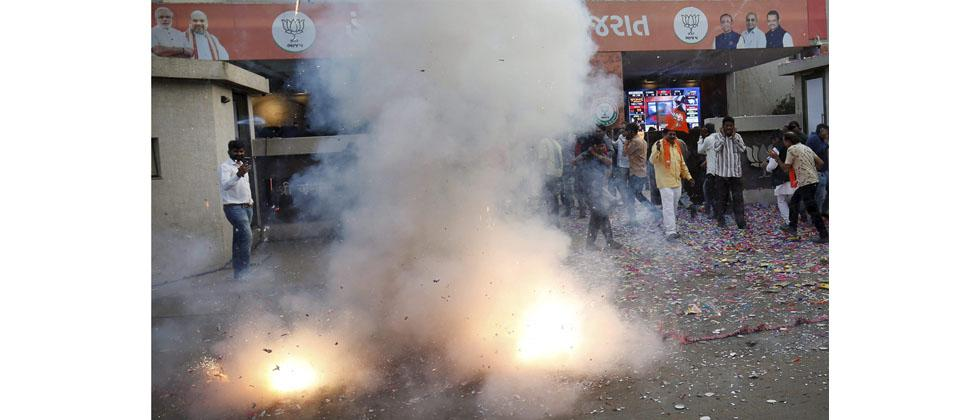 Supporters of Bharatiya Janata Party (BJP) burn firecrackers to celebrate the party's victory in Gujarat assembly elections in Gandhinagar on Monday. PTI Photo