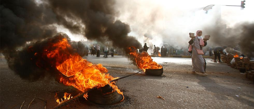 A Sudanese protester walks past burning tyres as military forces tried to disperse the sit-in outside Khartoum's army headquarters on June 3, 2019. AFP Photo