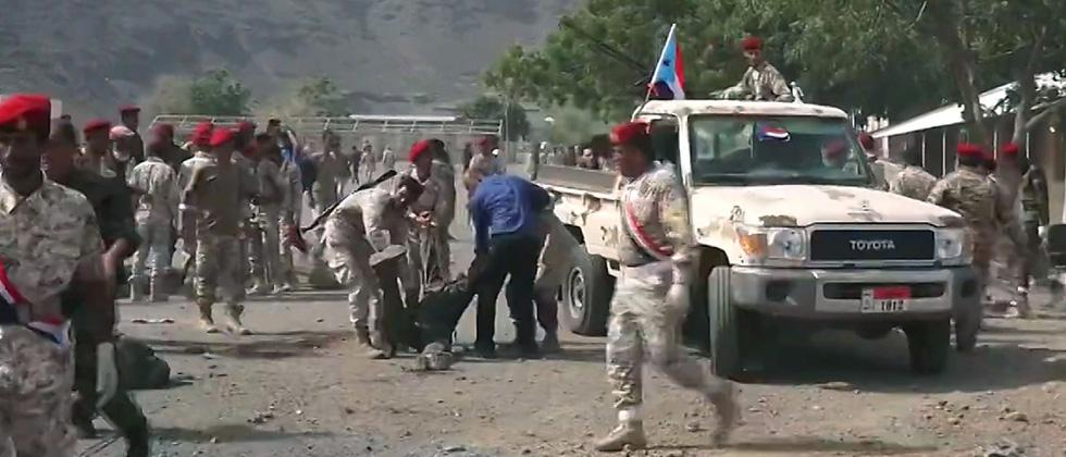 A screen grab from a video made on Thursday, shows Yemeni security forces carrying a body at the scene of a missile attack on a military camp west of Yemen's government-held second city Aden.