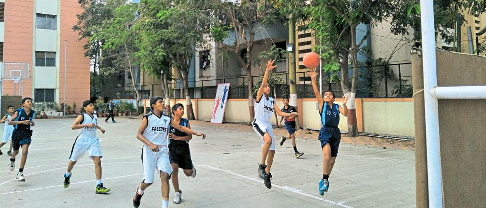 The players of Millennium School (in blue) in action against Falcon Basketball Academy