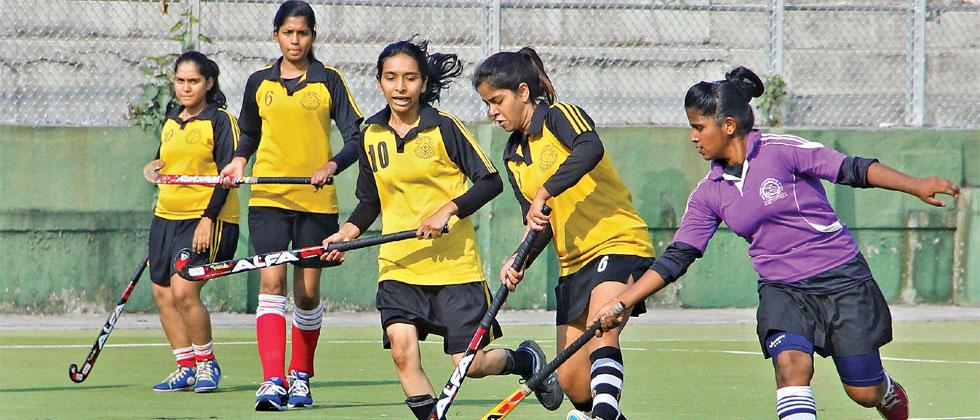 Girls from St Claire's High School (in yellow) control the ball during their match against PCMC School