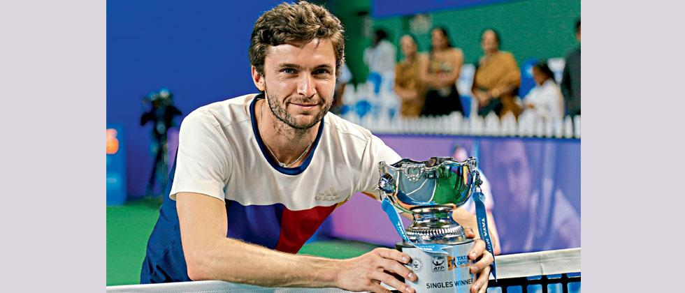 Gilles Simon poses with the winner's trophy after beating Kevin Anderson in the final at Balewadi Sports Complex