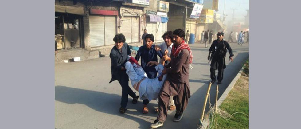 Pakistani residents carry an injured man after a twin blasts at a market in Parachinar, capital of Kurram tribal district, on June 23, 2017.
