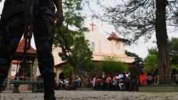 Military personnel stand guard during a mass outside St Sebastian's Church in Negombo on May 9, 2019. AFP Photo