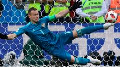 Russia's goalkeeper Igor Akinfeev stops a shot by Spain's forward Iago Aspas during the penalty shootout of the Russia 2018 World Cup round of 16 football match between Spain and Russia at the Luzhniki Stadium in Moscow on Sunday