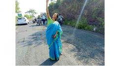 NCP MP Supriya Sule taking a selfie with a  pothole-ridden road near Pune.
