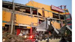 A photograph taken and released on  Friday by Indonesia's National Agency for Disaster Management (BNPB) shows a collapsed shopping mall in Palu, Central Sulawesi, after a strong earthquake hit the area.