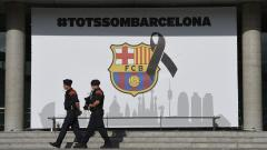 "Armed Catalan policemen, known as Mosso d'Esquadra pass by the FC Barcelona logo with a black ribbon and a message reading ""We are all Barcelona"" before the Spanish league footbal match FC Barcelona vs Real Betis at the Camp Nou stadium in Barcelona on A"