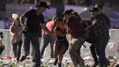 People carry a person at the Route 91 Harvest country music festival after gun fire was heard on October 1, 2017 in Las Vegas, Nevada. AFP Photo