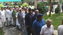 Men stand in a queue before casting their vote during Pakistan's general election at a polling station in Lahore on July 25, 2018. Wakil Kohsar/AFP