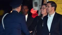 US Defense Secretary Mark Esper (R) and his wife Leah are greeted as they arrive at Sydney Airport on Friday.