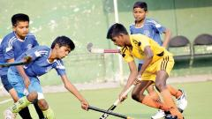 A player from PCMC School (in yellow) hits the ball during their match against Jyoti English Medium School at Major Dhyan Chand Poligras Stadium in Pimpriq