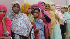 Pakistani women stand in a queue as they wait to cast their vote outside a polling station during general election in Lahore on Wednesday.