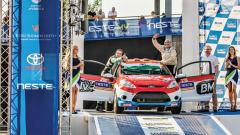 Sanjay Takale (right) waves while his co-driver Darren Garrod acknowledges on the finish ramp of WRC Rally Finland.