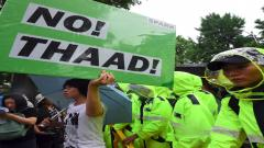 """A South Korean protestor holds up a placard reading """"No THAAD!"""" during a rally against the deployment of the US Terminal High Altitude Area Defense (THAAD) system near the presidential Blue House in Seoul on July 31, 2017."""