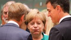 Germany's Chancellor Angela Merkel (C) reacts as she speaks with European Council President Donald Tusk (L) and Spain's Prime Minister Pedro Sanchez during an EU leaders' summit focused on migration, Brexit and eurozone reforms on Thursday in Brussels.