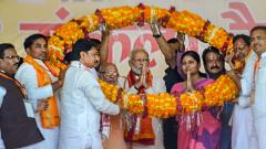 Prime Minister Narendra Modi with NDA candidate for Mirzapur parliamentary seat Anupriya Patel (R) being garlanded during an election campaign rally for the ongoing Lok Sabha polls, in Mirzapur on May 16, 2019. PTI Photo