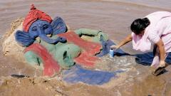 Sand artist gives finishing touches to a sand sculpture of Lord Ganesh at Juhu Chowpatty in Mumbai.