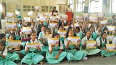 School students hold up the placards of red dot campaign.