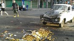 A handout picture released by the official Syrian Arab News Agency (SANA) on Wednesday shows a member of the Syrian security forces walking past a truck damaged in a suicide attack in the southern city of Sweida.
