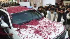 Pakistani police officials and suppoeters escort a vehicle carrying the head of the Jamaat-ud-Dawa (JuD) organisation Hafiz Saeed as he leaves after his release order by a court in Lahore on November 22, 2017