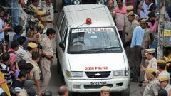 A hearse van drives out carrying bodies of victims drives out near the site where 11 family members were found dead inside their home in the neighbourhood of Burari in New Delhi on Sunday.