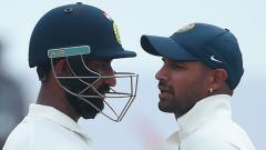 Indian cricketers Shikar Dhawan (R) and Cheteshwar Pujara talk during the first day of the first Test match between Sri Lanka and India