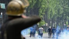 Police fire tear smoke shells towards Kashmiri protestors at Mirgund Pattan on the outskirts of Srinagar on May 13, 2019, as protesters called for justice in the case of the alleged rape of a three-year-old girl. AFP Photo