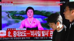 People walk past a television news screen showing a North Korean announcer reading a statement on the country's new ICBM test, at a railway station in Seoul on November 29, 2017