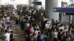 Passengers stranded overnight at the Kansai International Airport due to typhoon Jebi queue for buses that will transport them from the airport in Izumisano city, Osaka prefecture on Wednesday.